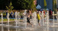 Photo: Kids running through the fountain at the splash pad at Elstro Plaza