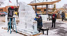 Photo: Ice Carvers work on globe sculpture.