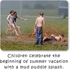 Children celebrate the beginning of summer vacation with a mud puddle splash!