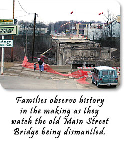 Families observe history in the making as they watch the old Main Street Bridge being dismantled.