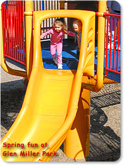 Spring fun at Glen Miller Park.  (Two children play on a slide.)