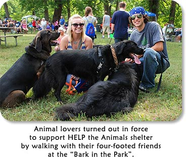 "Photo: 3 black dogs with their owners.  Text: Animal lovers turned out in fource to help support HELP the Animals shelter by walking with their four-footed friends at the ""Bark in the Park""."