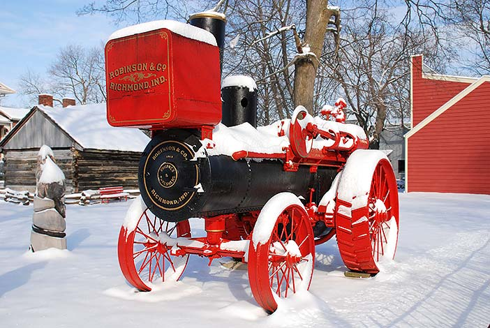 Photo: Red and black Robinson & Co. steam tractor sitting in snow.
