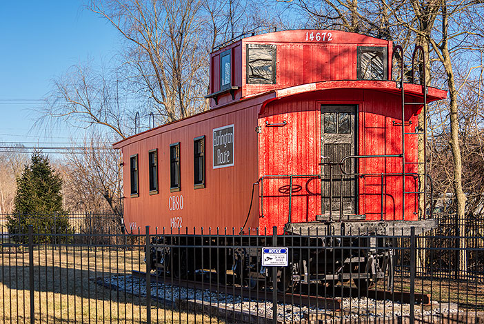Photo: Red caboose car behind black fence.