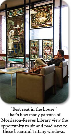 "Man reading next to Tiffany stained glass windows.  ""Best seat in the house!"" That's how many patrons of Morrisson-Reeves Library view the opportunity to sit and read next to these beautiful Tiffany windows."